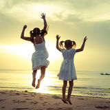 Happy children jumping on the beach. At the dawn time Royalty Free Stock Photography