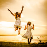 Happy children jumping on the beach. At the dawn time Royalty Free Stock Image