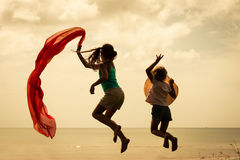 Happy children jumping on the beach. On the dawn time Stock Images