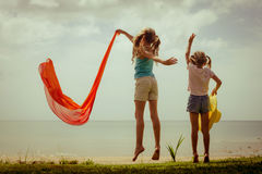 Happy children jumping on the beach. On the dawn time Royalty Free Stock Images