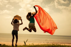 Happy children jumping on the beach. On the dawn time Stock Photos