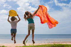 Happy children jumping on the beach. On the day time Stock Photo