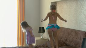 Happy children jumping on the bed and having fun. Happy little sisters jumping on the bed and having fun stock video