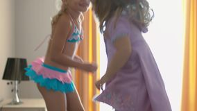 Happy children jumping on the bed and having fun. Happy little sisters jumping on the bed and having fun stock video footage