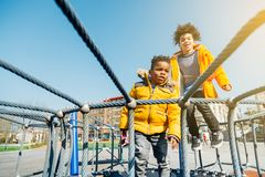Happy children jumping on elastic bed outdoors. Two children with yellow coats jumping on elastic bed in a playground in a sunny day Stock Photos