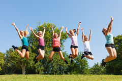 Happy children jumping. Group of six happy children jumping on meadow Royalty Free Stock Photo