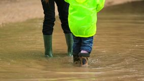 Happy Children Jumping In Huge Puddle. Wait down shot of two happy children in bright green jackets and rubber boots jumping and playing in huge puddle in the stock footage