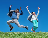 Happy children jumping on meadow Stock Image