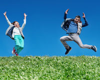 Happy children jumping on meadow Stock Photography