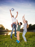 Happy children jumping and playing with ball. Outdoors. Sunny summer day Stock Image