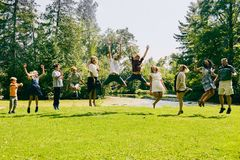 Happy children jumping with their parents. Happy children jumping together with their parents in park during summer vacations Stock Images