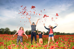 Happy children jumping and throwing petals of poppies. Summer, childhood, leisure concept. Happy children jumping and throwing petals of poppies on the field at Royalty Free Stock Images
