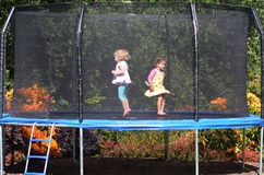 Happy children jumping on trampoline. Two happy girls jumps on a trampoline Royalty Free Stock Photography