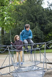 Happy children jumping on a trampoline or elastic bed. In a park in autumn in Dusseldorf, Germany Stock Image