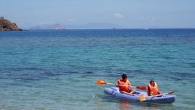 Happy children kayaking on beach. Two happy children kayaking together on the tropical beach with blue water and beautiful landscape in Labuan Bajo at Flores stock video footage