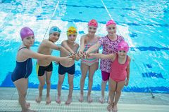 Happy children kids group at swimming pool class learning to swim.  royalty free stock photography