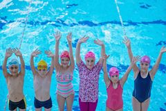Happy children kids group at swimming pool class learning to swim.  royalty free stock image