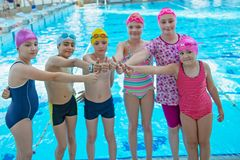 Happy children kids group at swimming pool class learning to swim.  stock photo