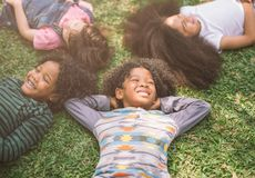 Happy children kids laying on grass in park royalty free stock photos