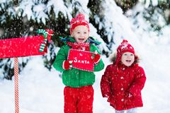 Child with letter to Santa at Christmas mail box in snow Royalty Free Stock Photography