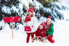Children with letter to Santa at Christmas mail box in snow. Happy children in knitted reindeer hat and scarf holding letter to Santa with Christmas presents Stock Photos