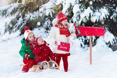 Children with letter to Santa at Christmas mail box in snow. Happy children in knitted reindeer hat and scarf holding letter to Santa with Christmas presents Royalty Free Stock Photo