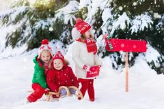 Children with letter to Santa at Christmas mail box in snow. Happy children in knitted reindeer hat and scarf holding letter to Santa with Christmas presents Royalty Free Stock Photography
