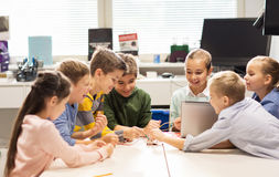 Happy children with laptop at robotics school. Education, children, technology, science and people concept - group of happy kids with laptop computer building Stock Images