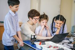 Happy children learn programming using laptops on extracurricular classes stock images