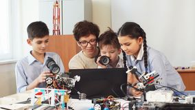 Happy children learn programming using laptops on extracurricular classes. Curious clever pupils with the help of their female teacher doing a group project stock video footage