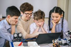 Happy children learn programming using laptops on extracurricular classes stock image