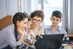Happy children learn programming using laptops on extracurricular classes stock photo
