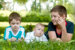 Happy children lie on the green grass in the park Stock Photo