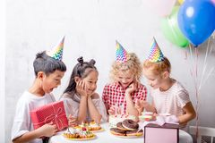 Happy children looking at the candles of the cake while standing at the table stock photography