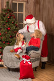 Happy children looking at Santa Claus. Happy children sitting on grey armchair and looking at Santa Claus Stock Photography