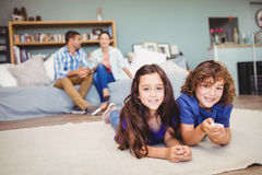 Happy children lying on carpet while parents in background Royalty Free Stock Photos