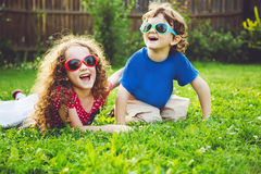 Happy children lying on the grass. Focus on a girl. Stock Photos