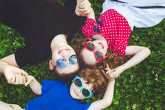 Happy children lying on the grass holding hands. Royalty Free Stock Photography