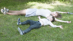 Happy children lying on grass in summer park, brother and sister Stock Photo