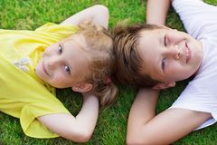 Happy children lying on green grass at backyard royalty free stock photography