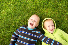 Happy children lying on green grass Stock Photos