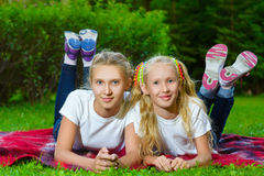 Happy children lying on green grass outdoors in Stock Photography