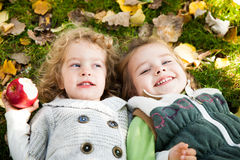 Happy children lying outdoors Stock Images