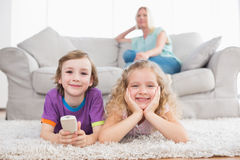 Happy children lying on rug while woman sitting on sofa Stock Photos