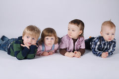 Happy children lying on white floor Royalty Free Stock Photos