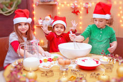 Happy children making cookies royalty free stock photography