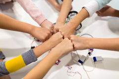 Happy children making fist bump at robotics school. Education, children, technology, science and people concept - group of happy kids with building kit making Royalty Free Stock Image