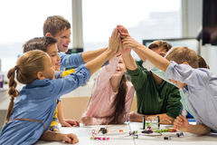Happy children making high five at robotics school. Education, children, technology, science and people concept - group of happy kids building robots and making Royalty Free Stock Images