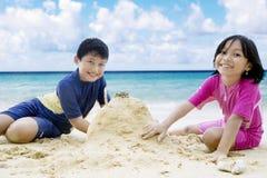 Happy children making sandcastle Stock Photos