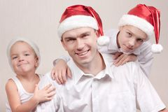Happy children and man in santa hat Stock Photography